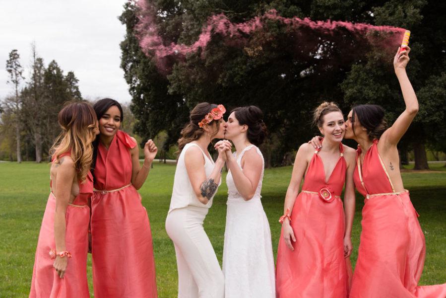 les mariées s'embrassant entourées de leurs demoiselles d'honneur