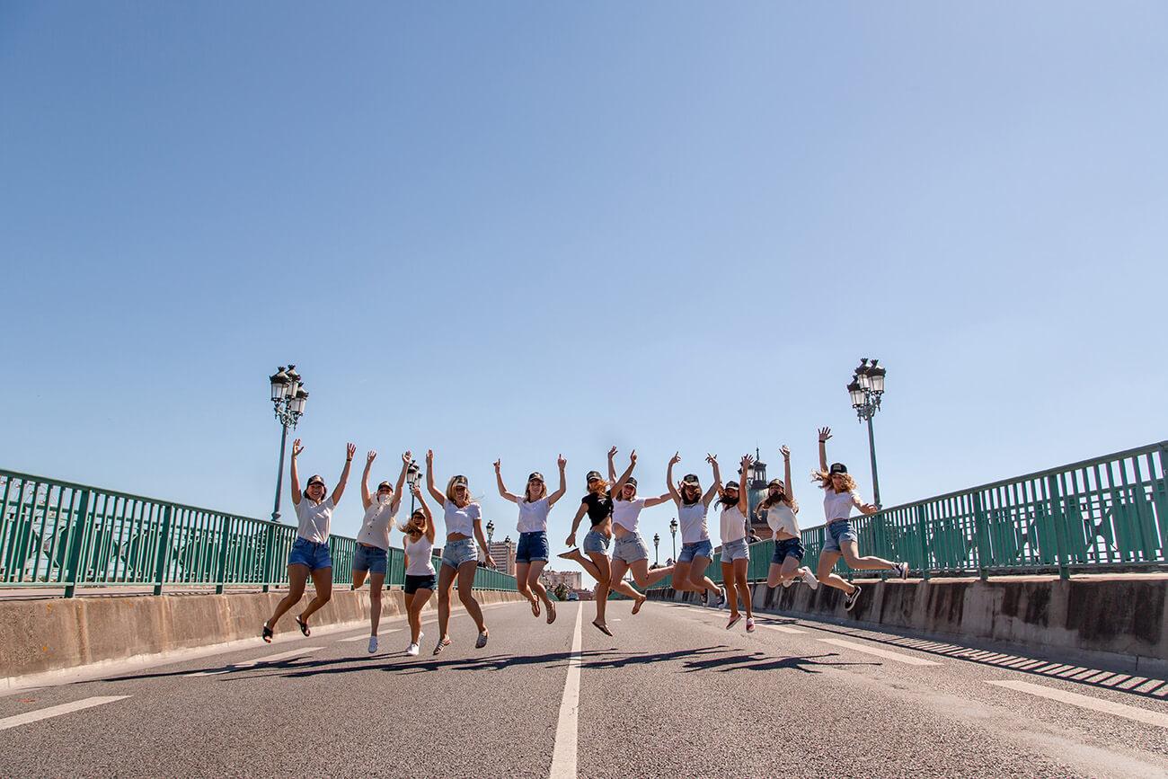 Photo d'une future mariée et de ses amies sautant de joie pendant une séance photos EVJF à Toulouse